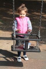 bambina che spinge una bambola sull'altalena