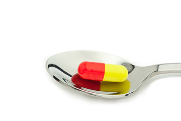 red and yellow tablet in spoon