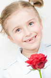 Happy little girl with red rose - portrait