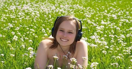 Frau hört Musik auf einer Wiese