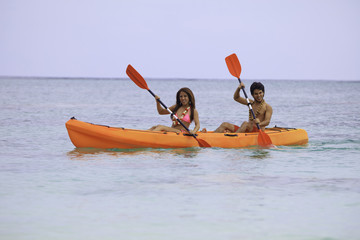 young asian couple in their kayak in hawaii
