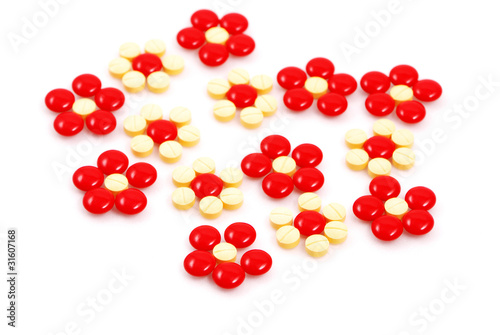 Flower made of red and yellow medicinal pills  on white backgrou