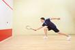 Squash player hitting a ball in a squash court