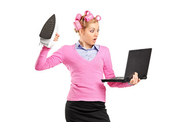 Woman with hair rollers holding an iron and looking at laptop