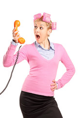 Young woman with hair rollers yelling on a phone