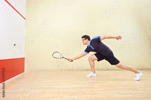 Squash player hitting a ball in a squash court