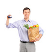 Smiling man holding a credit card and a bag full with vegetables