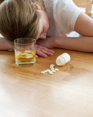 close up of pills and alcohol with suicidal woman to background