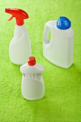 three plastic white bottles on green background
