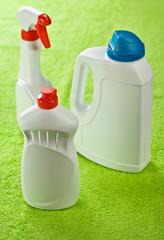 three white bottles on green background