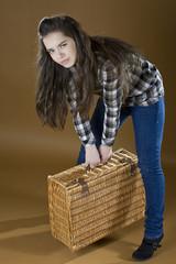девушка пытается поднять тяжелый чемодан