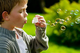 a young child blowing bubbles