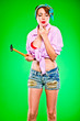 Girl blowing on fingers striked by hammer. Pin-up and retro.