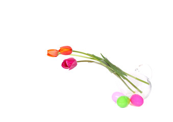 colourful tulips glass vase surrounded by easter eggs isolated