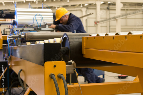 Worker using steel coil processing machine focus on machine.