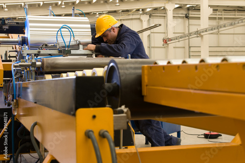 Worker using steel coil processing machine focus on worker.