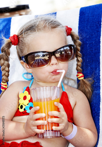 Child in glasses and red bikini drink juice.