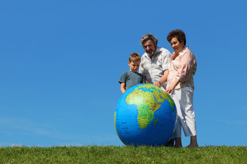 boy and grandparents standing on lawn and looking on globe