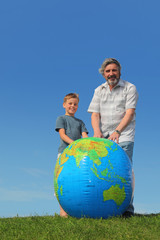boy and his grandfather standing on lawn near big globe