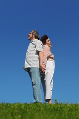 old woman and man standing on summer lawn back to back