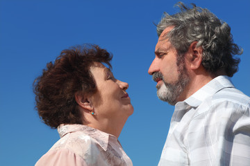 old woman and man looking to each other, blue sky