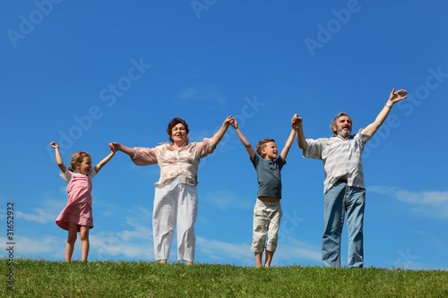 grandchildren and their grandparents standing on lawn and holdin