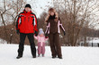 father, mother and little daughter standing at snow