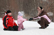 daughter goes from father to mother at snow in winter