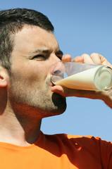 man is drinking fresh glass of milk in the blue skye