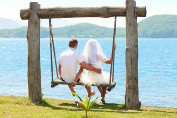 Groom and bride on a swing