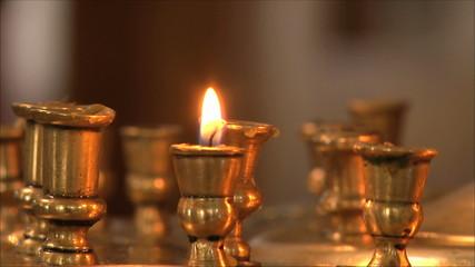 одна свеча в церкви, крупный план, размытый фон