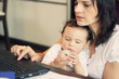 Mother in front of the laptop with baby talking on cellphone