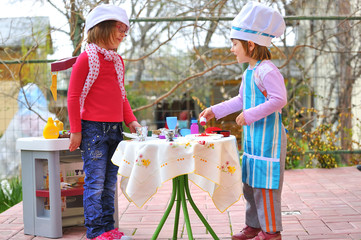 little girls having fun playing cooking