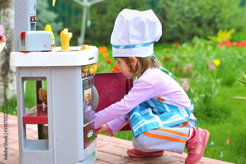 Little girl having fun playing cooking