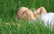 Junge Frau liegt auf grüner Wiese