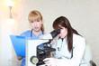 顕微鏡をのぞく医師と困惑した表情でメモをとる看護師