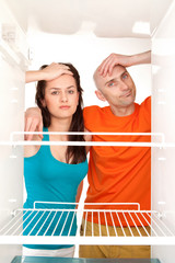 Couple with empty refrigerator