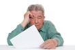 Sorgenvoller Senior sitzt vor Rechnungen