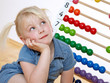 Little blond child using an abacus to learn