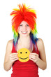 young beauty woman in multicolored clown wig smiling and holding
