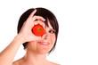Junge Frau hält Tomate vor ihr Auge