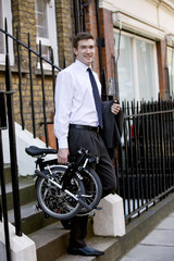 A businessman leaving a building, holding a bicycle