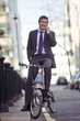 A businessman on his bicycle, talking on a mobile phone