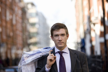 A businessman carrying his dry cleaning