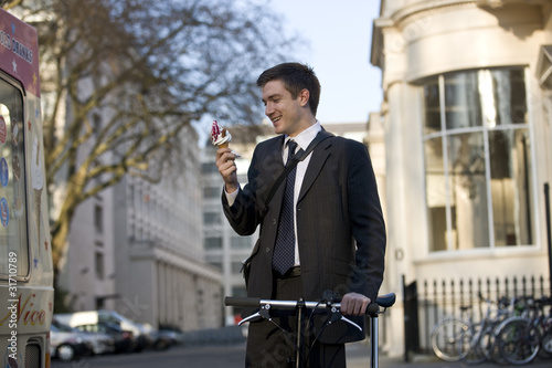 A businessman holding his bicycle, eating an ice cream