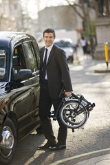 A businessman standing next to a taxi, holding folded bicycle
