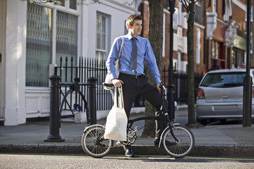A businessman holding his bicycle, carrying shopping bags