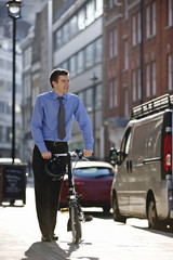 A businessman pushing his bicycle along the street