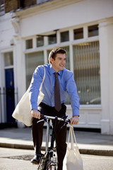 A businessman riding his bicycle, carrying shopping bags
