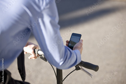 A businessman on his bicycle, looking at his mobile phone